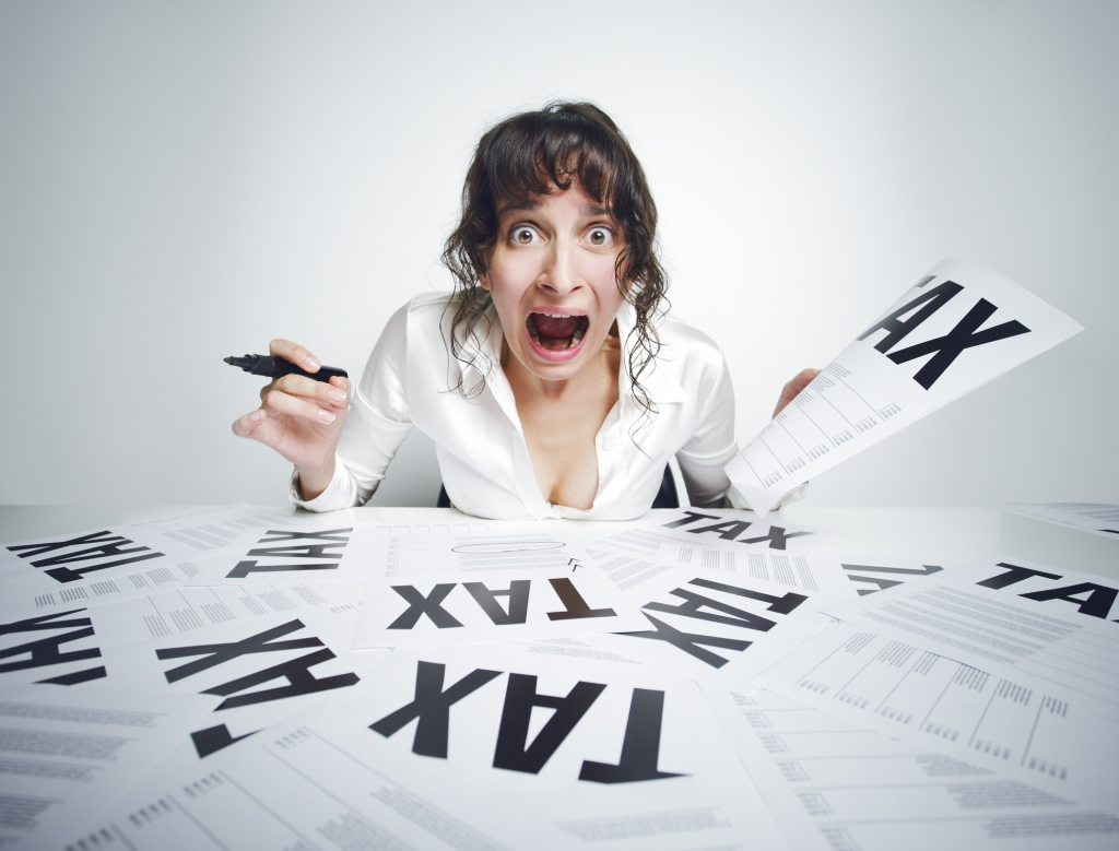 Panicked women screaming over a cluttered pile of tax work